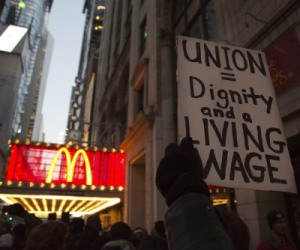 Image: A protester holds up a sign at a demonstration outside McDonald's in Times Square in New York